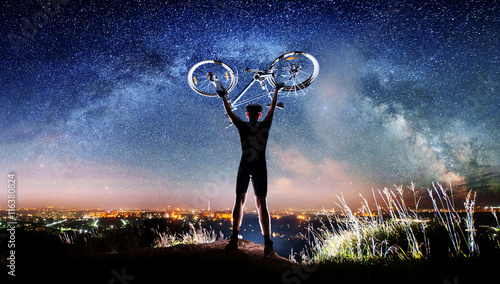 Strong biker hold his bike above in the hands on the top of the mountain nearly city. Milky way and night city shining on the background