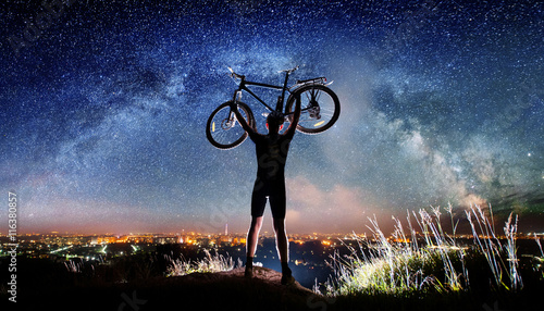 Silhouette of biker hold his bicycle above in the hands on the top of the mountain nearly city. Milky way and night city shining on the background