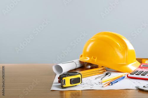 Fototapeta Construction blueprints with tools and helmet on light background obraz na płótnie