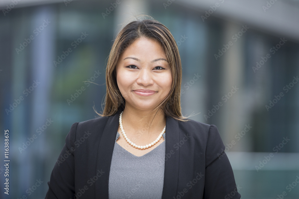 Fototapeta Asian businesswoman in smart business suit standing outside.