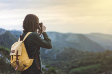 Hipster Young Girl With Bright Backpack Taking Photo Of Amazing Landscape Sunset On Vintage Camera On Peak Of Foggy Mountain Mockup. Tourist Traveler On Background Sunlight In Trip, Mock Up For Text.
