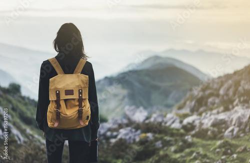 Foto  Hipster girl with backpack enjoying sunset on peak foggy mountain
