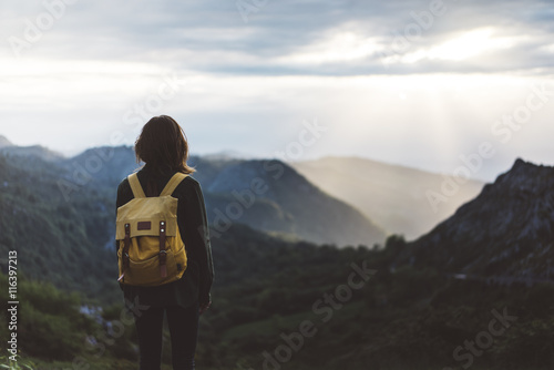 Fotografía Hipster girl with backpack enjoying sunset on peak foggy mountain