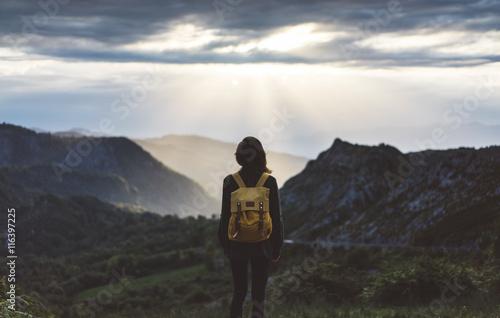 Fototapeta Hipster girl with backpack enjoying sunset on peak foggy mountain. Tourist traveler on background valley landscape view mockup. Hiker looking sunlight in trip Northern Spain Picos de Europa mock up obraz