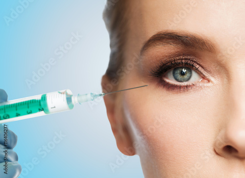 Fotografía  woman face and hand with syringe making injection