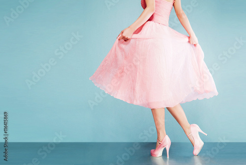 Leinwand Poster Romantic pink dress with pink shoes on vintage look blue background