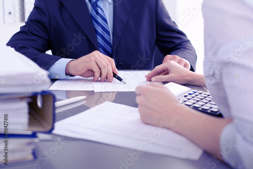 Fotografiet  Bookkeepers or financial inspector making report, calculating or checking balance