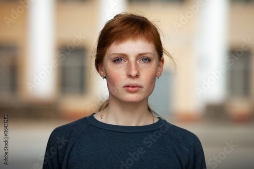 Fotografiet  Young redhead caucasian woman serious face outdoor portrait