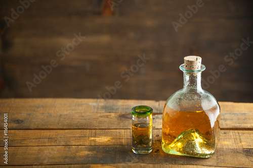 Photo Gold tequila in glass on wood table