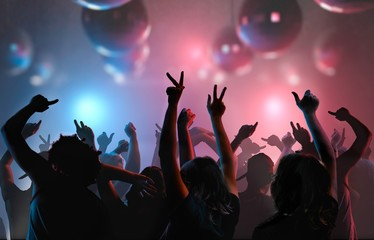 Nightlife and disco concept. Silhouettes of young people are enjoying and dancing in club.