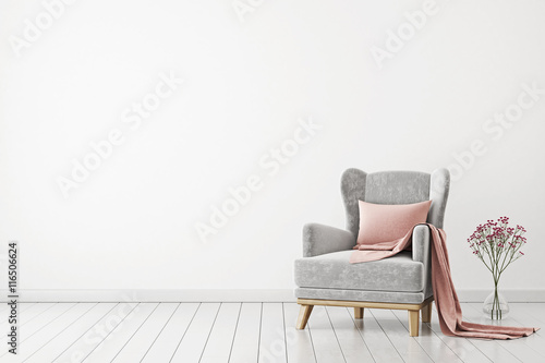 Fotografia Neutral interior with velvet armchair on empty white wall background