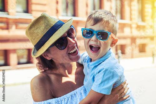Small boy in sunglasses laughing in his mother's arms during wal