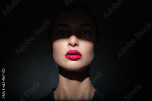 Fotografía  Beautiful model with bright pink lips and face half covered in shadow