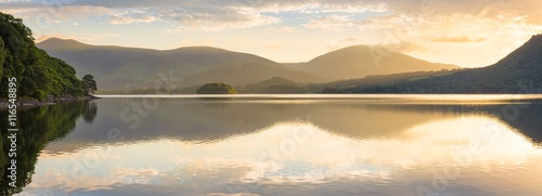Obraz Golden sunlight shining through mountains on peaceful calm morning at Derwentwater, Lake District, UK. - fototapety do salonu