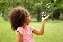 Afro-American Little Girl Catching Soap Bubbles