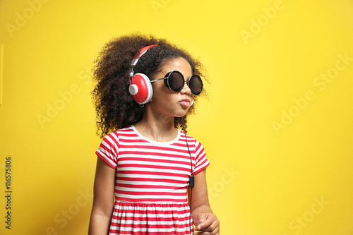 Papiers peints Magasin de musique Afro-American little girl with headphones listening to music on yellow background