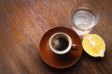 Cup Of Coffee With Lemon And Water On Table