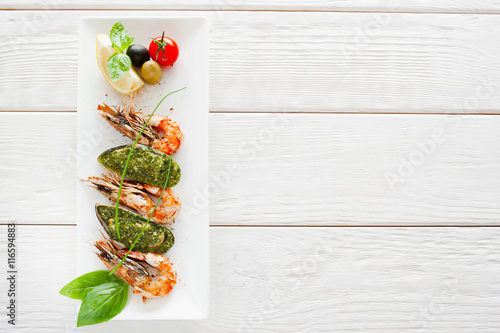 Poster Coquillage Plate with prepared seafood on white wooden background, copy space. Vertical position of dish with stuffed mussel and grilled shrimp, menu photo, free space for text