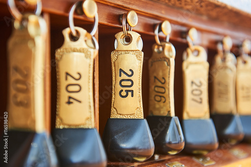 hotel keys with room numbers hanging at reception