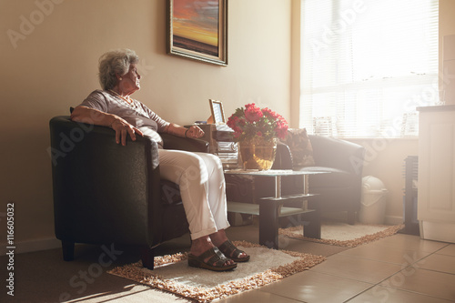 Fotografía  Senior woman sitting alone on a chair at home