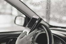 Closeup On Hand Holding Phone With Blank Display, Car Wheel Background