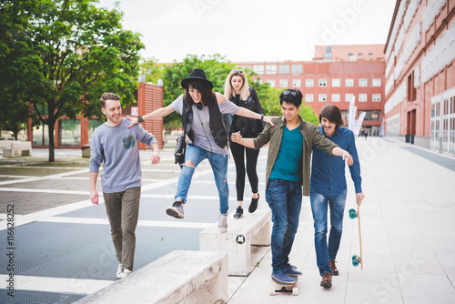 Foto op Plexiglas Art Studio Group of young multiethnic friends walking down the street laughing and chatting each other having fun - friendship, amusement, sportive concept