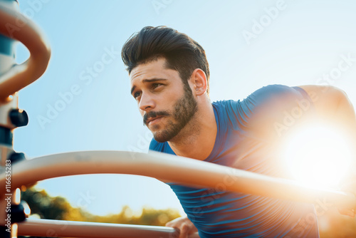 Muscular man during his workout outdoors Poster