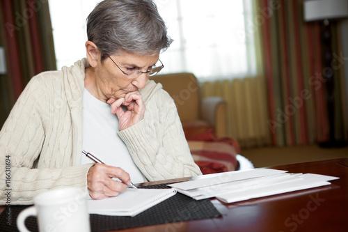 Fotografia, Obraz  Senior woman working on her bills