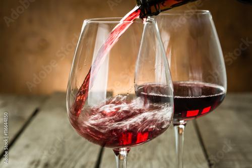 nalewanie-czerwonego-wina-na-drewnianym-tle