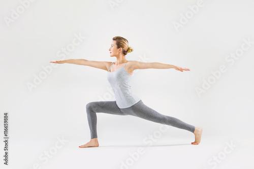 Poster  Schöne junge Frau auf einem grauen Hintergrund Studio Yoga tut