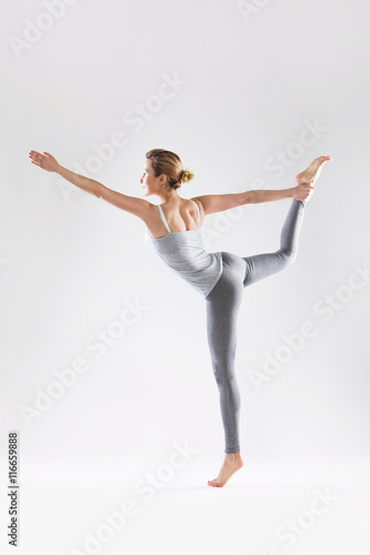 Leinwand Poster  Beautiful young woman doing yoga on a gray studio background