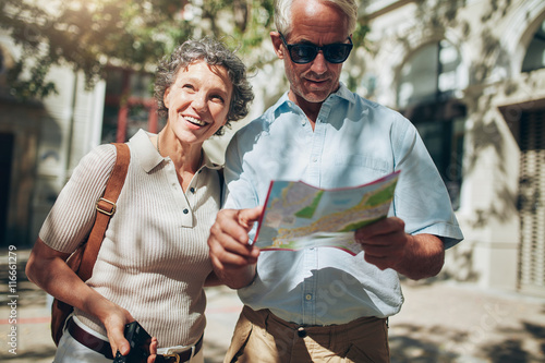 Fotografia  Mature man and woman using  map while sightseeing.