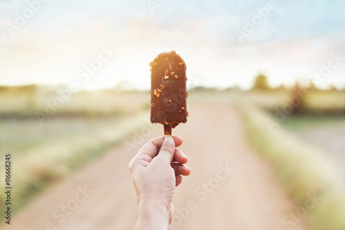 Printed kitchen splashbacks Chocolate Hand of woman holding a chocolate popsicle on nature background