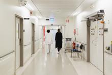 Rear View Of Women Walking At Hospital Corridor