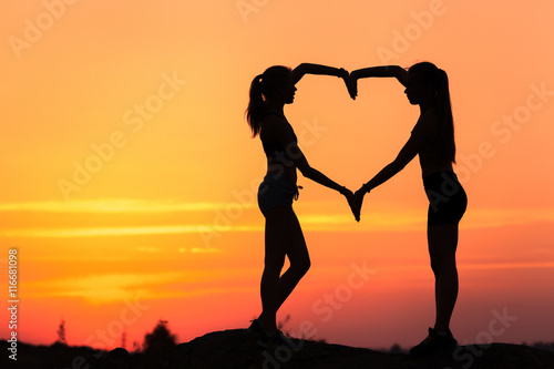 Papiers peints Corail Landscape with silhouette of young sporty women holding hands in heart shape on the background of colorful sky at sunset in summer time. Happy girls