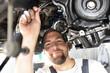 freundlicher Automechaniker repariert Motor eines Fahrzeuges in der Werkstatt // friendly car mechanic repairs engine of a vehicle in the garage