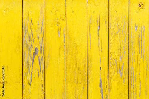 Vertical background of the wooden planks with cracked yellow paint