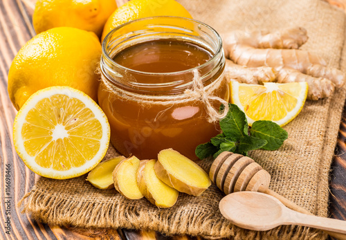 Honey comb, fresh lemon and ginger on a wooden table Canvas Print