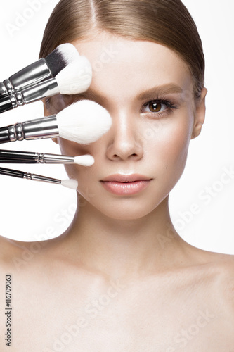 Photo  Beautiful young girl with a light natural make-up, brushes for cosmetics