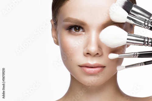 Beautiful young girl with a light natural make-up, brushes for cosmetics Canvas-taulu