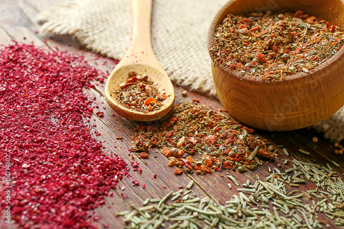 Fotografía  Mixed spices in bowl and spoon on wooden background