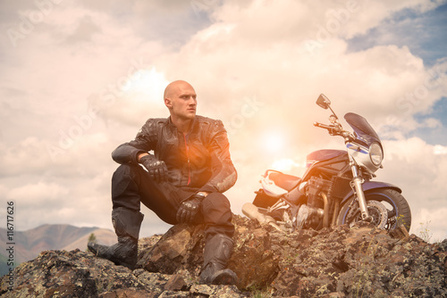 Photo  Bald rider sits on a mountain next to  motorcycle and looks asi