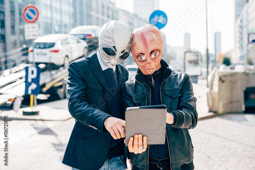 Canvas Two man wearing alien masks using tablet hand hold outdoor in city back light -