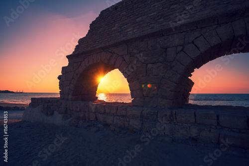 Aluminium Prints Ruins Remains of the ancient Roman aqueduct in ancient city Caesarea at sunset, Israel.