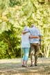 Frau hilft Senior mit Krücken