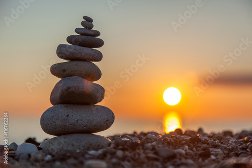 Fotografía The rock cairn on the beach, on a beautiful bright sunset