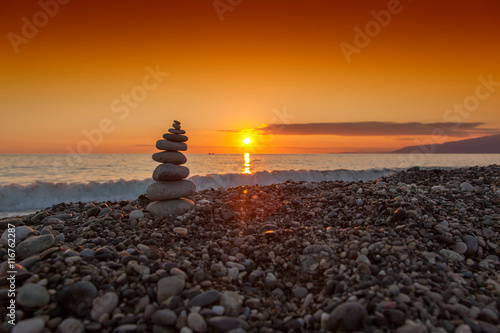 Leinwand Poster The rock cairn on the beach, on a beautiful bright sunset at the