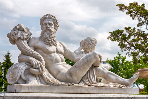 Marble statue of Greek Olympic god with cornucopia in his hands. Fototapeta
