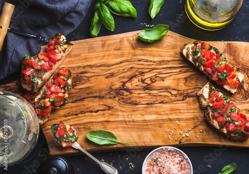 Papiers peints Entree Tomato and basil bruschetta with glass of white wine on olive wooden board over black background, top view, copy space, horizontal composition