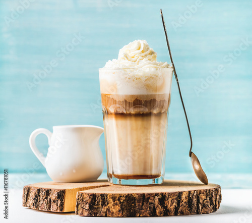 Fotografie, Obraz  Latte macchiato with whipped cream, serving silver spoon and pitcher on wooden r